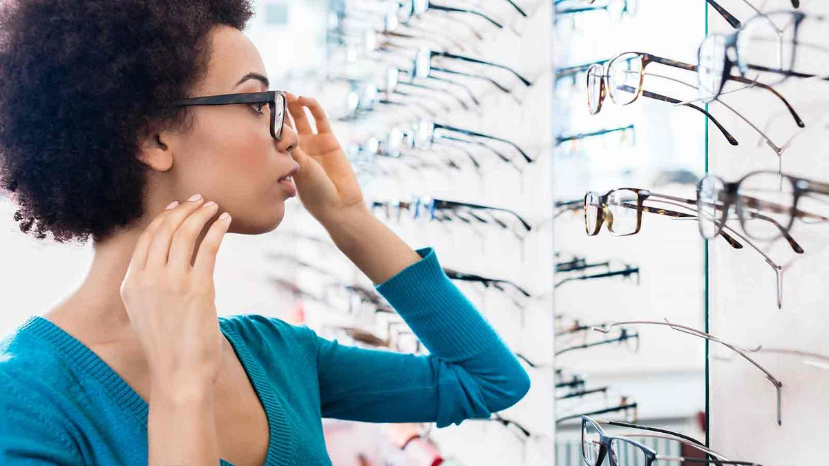 Woman trying on different eyeglass frames at the store