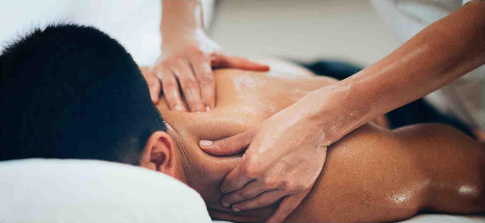 Massage therapist massaging shoulders of a male athlete