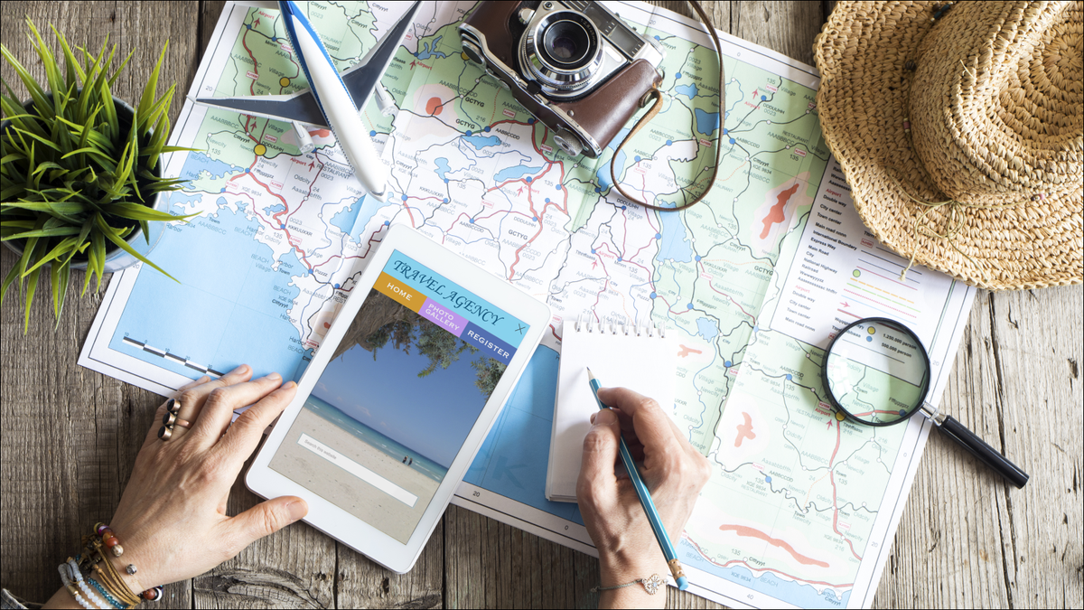 map, tablet, and other travel planning tools spread out on desk