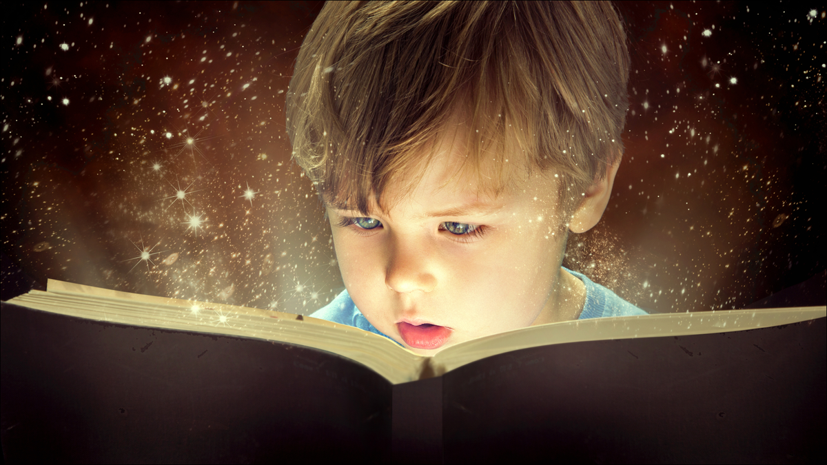 Child reading a book with magic sparkles flying out