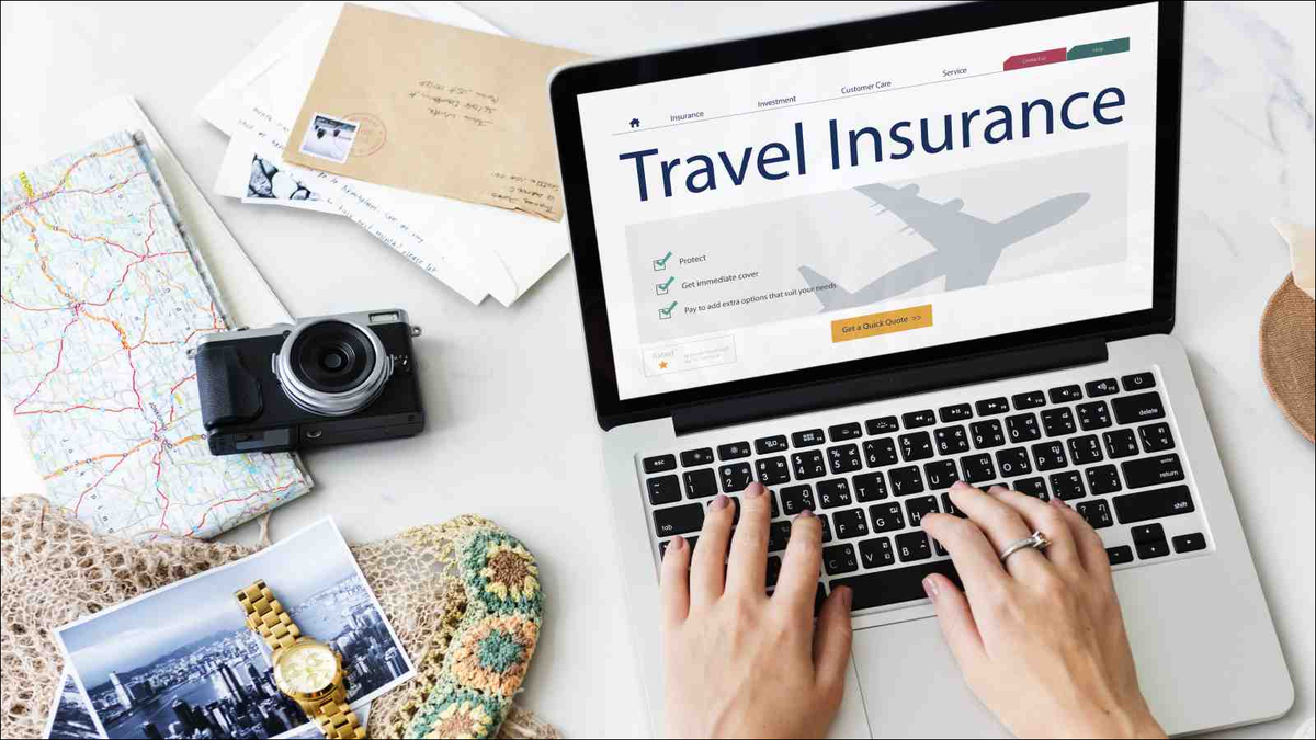 person looking up travel insurance on laptop