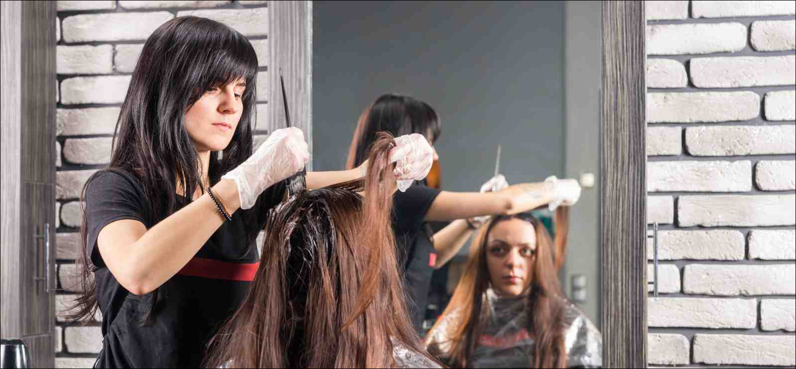 stylist coloring woman's hair