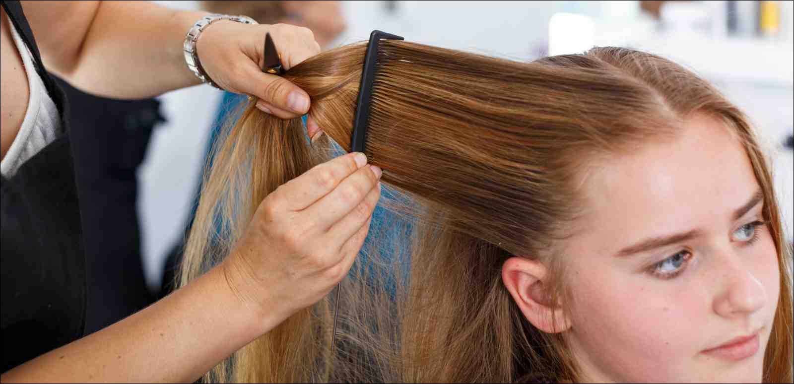 closeup of hairdresser styling teen girl's hair