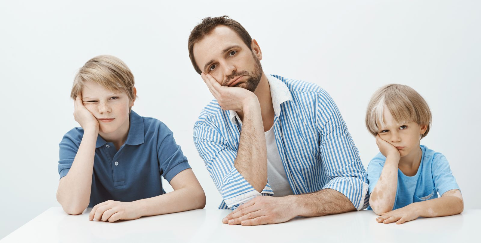 sons and dad sitting at table, leaning heads on palms and staring indifferent at camera