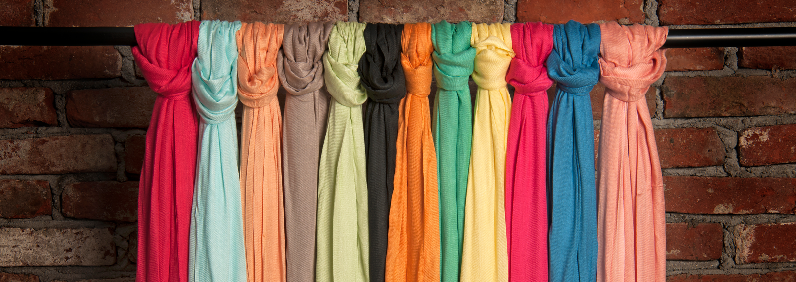 Colored scarves tied on the hanging bar on brick wall background
