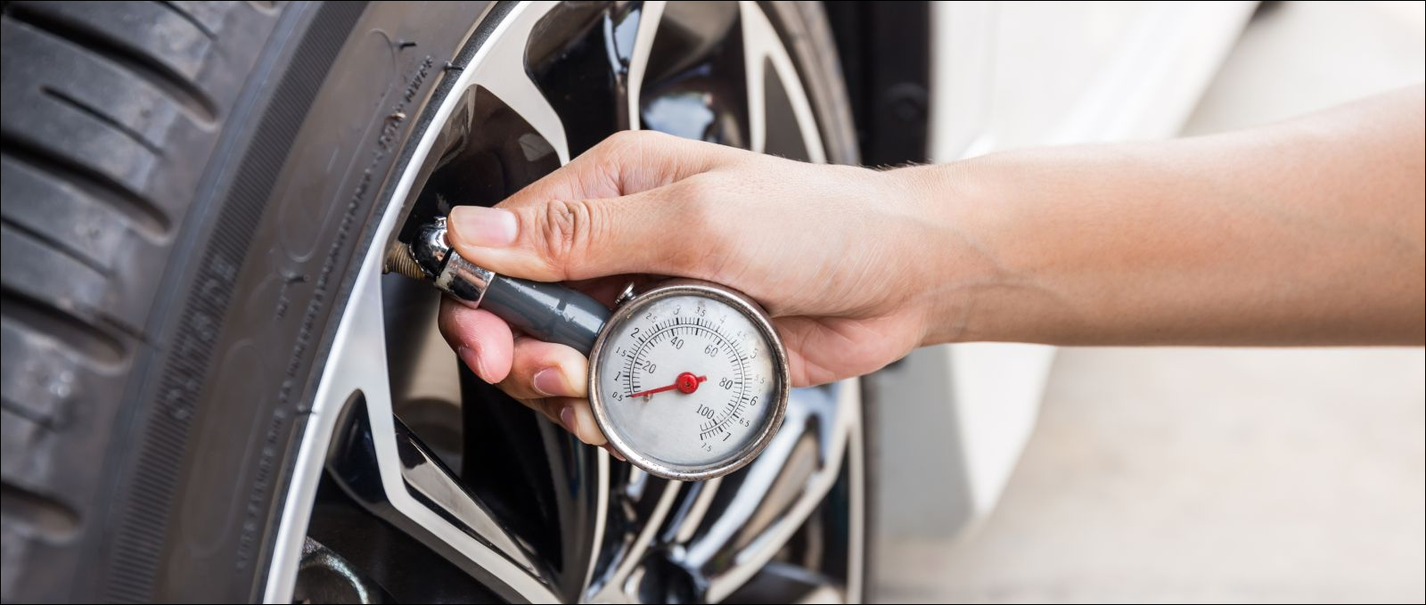 closeup of hand checking tire pressure with guage