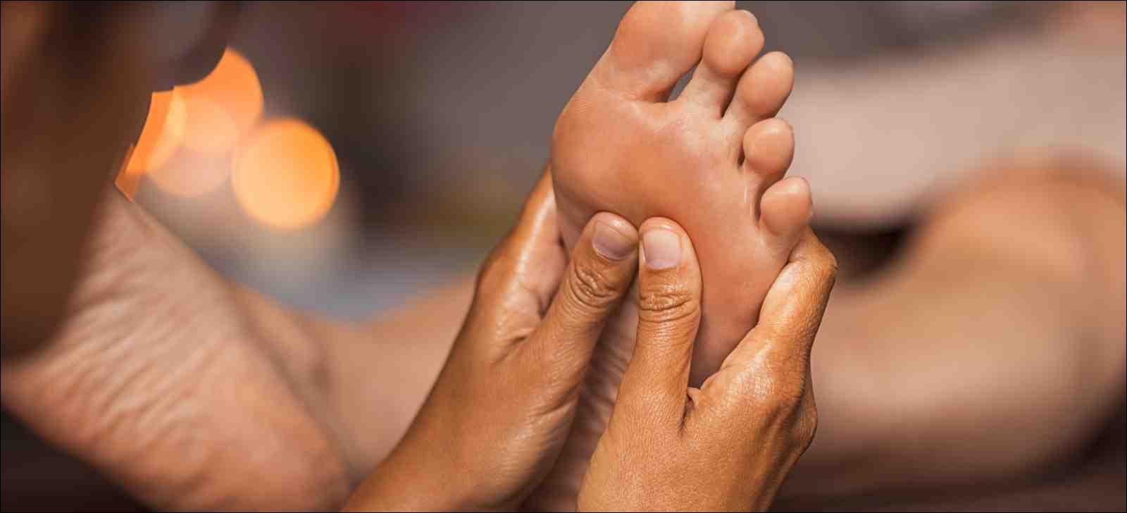 Closeup of masseuse doing foot reflexology to woman's foot