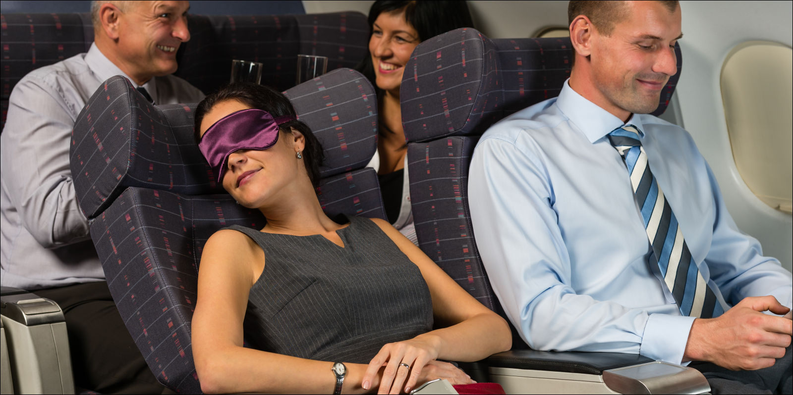 Business woman asleep during night flight among other airplane cabin passengers