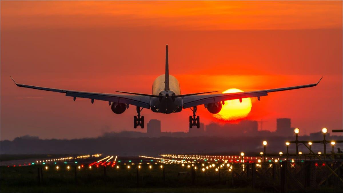 Passenger plane is landing during a wonderful sunrise