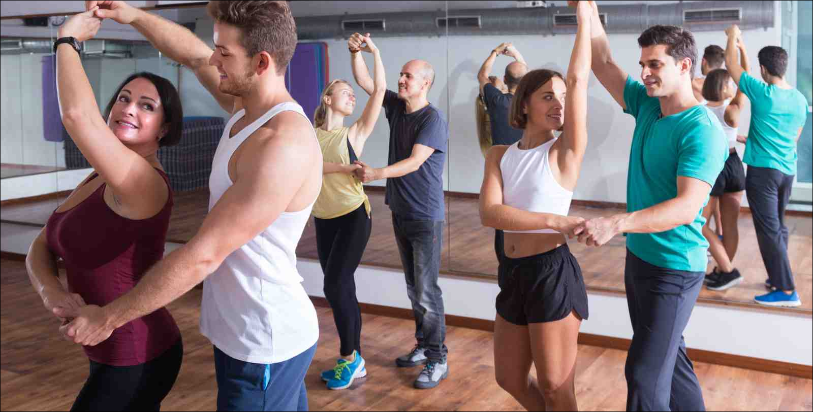 women and men in casual clothing learning dance moves
