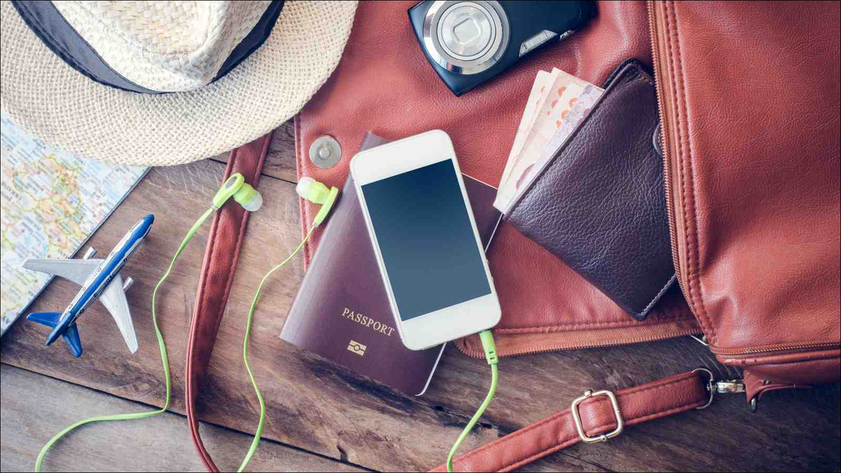 travel accessories laid out on desk with smartphone