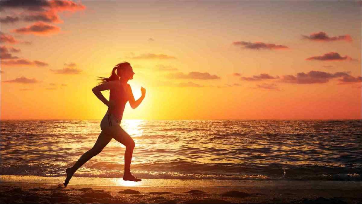 Woman Running In The Beach At Sunset