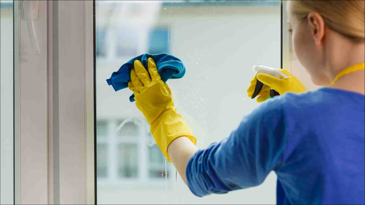 Young woman in yellow gloves cleaning window with blue rag and spray detergent