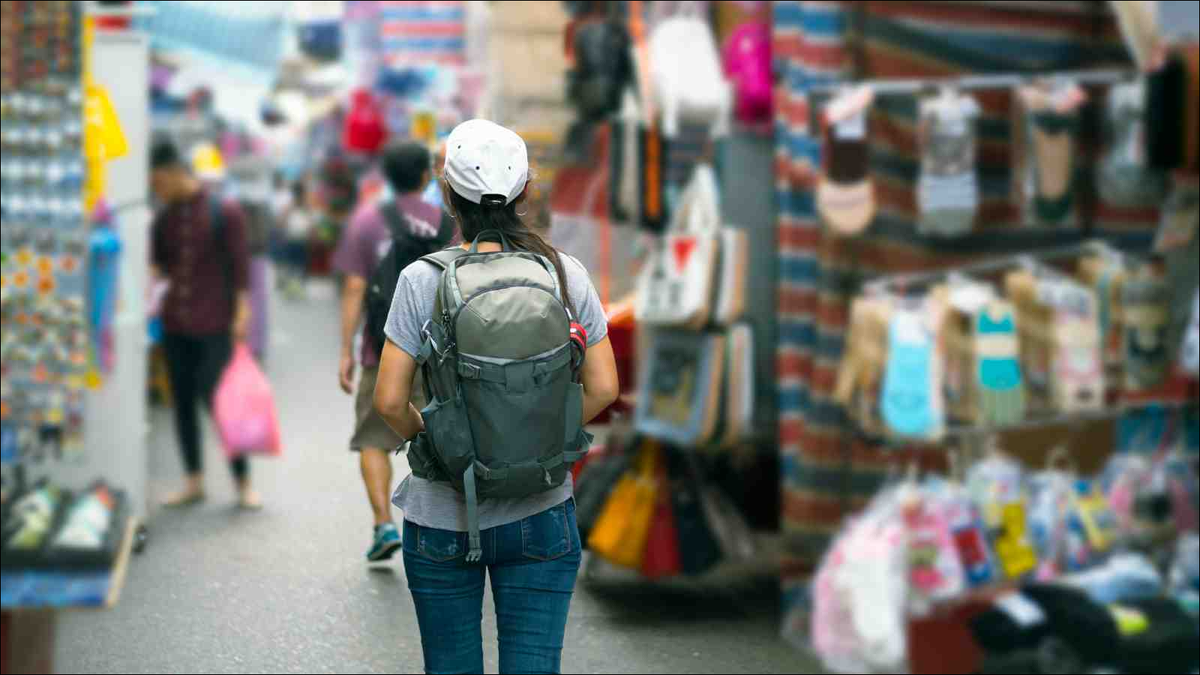 Female traveler with backpack walking market street