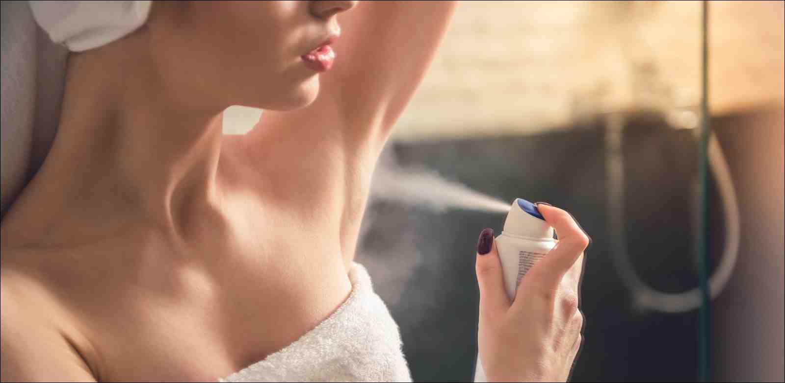 woman in bath towel applying antiperspirant after shower
