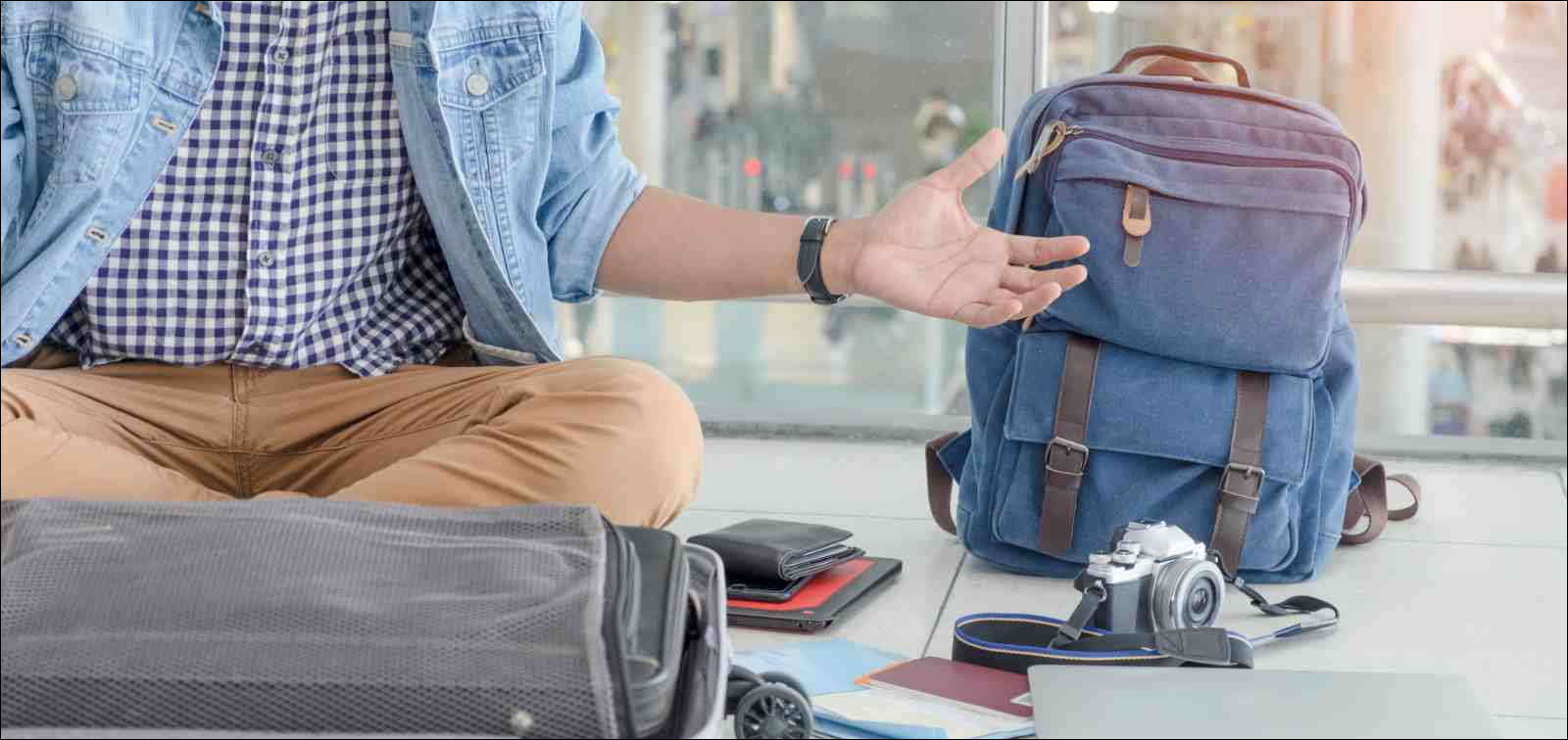 Young traveler sitting at the international airport, checking for lost or forgotten items