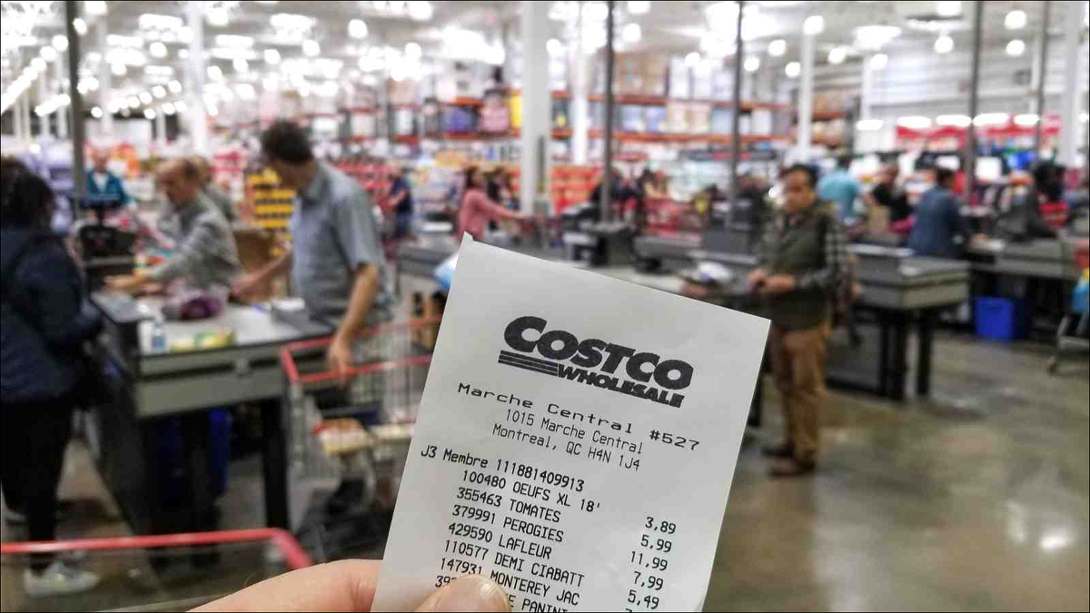 A hand holding a receipt with the brand name and logo in Costco warehouse