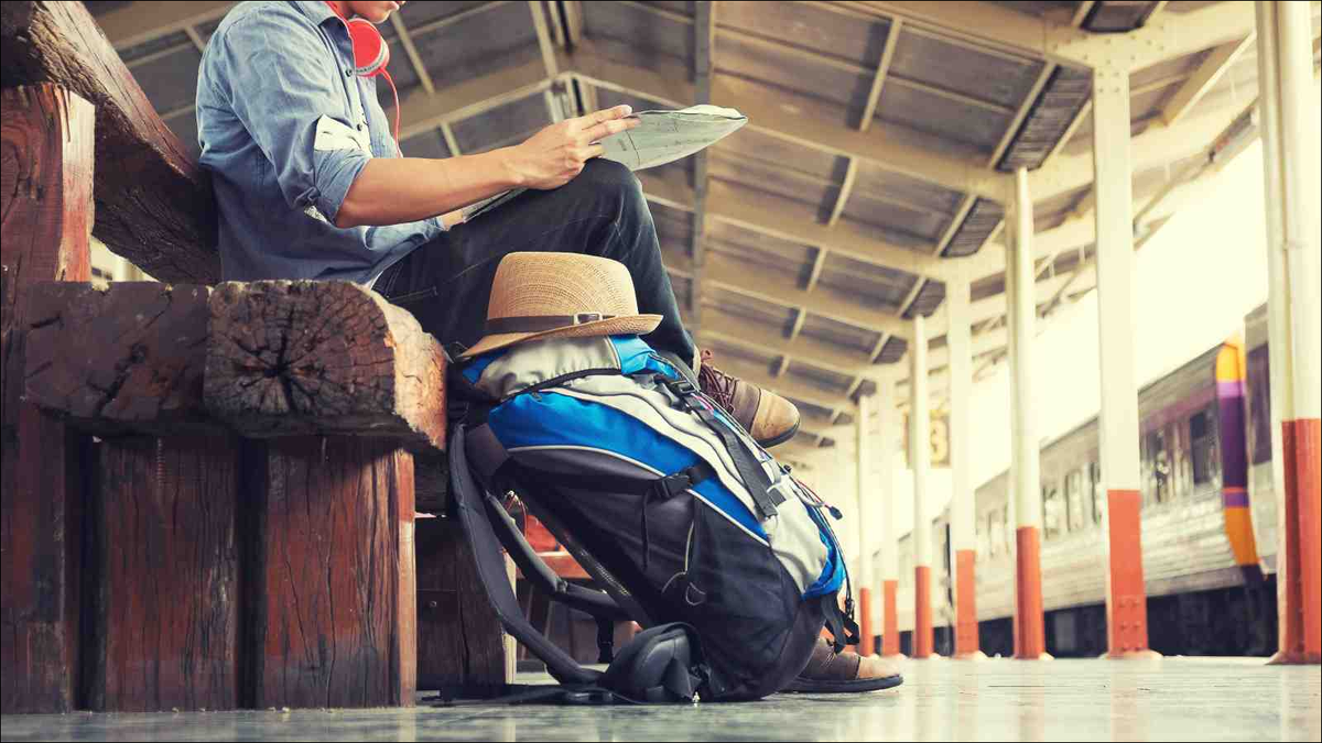 A man sitting with map. travel bag at the train station
