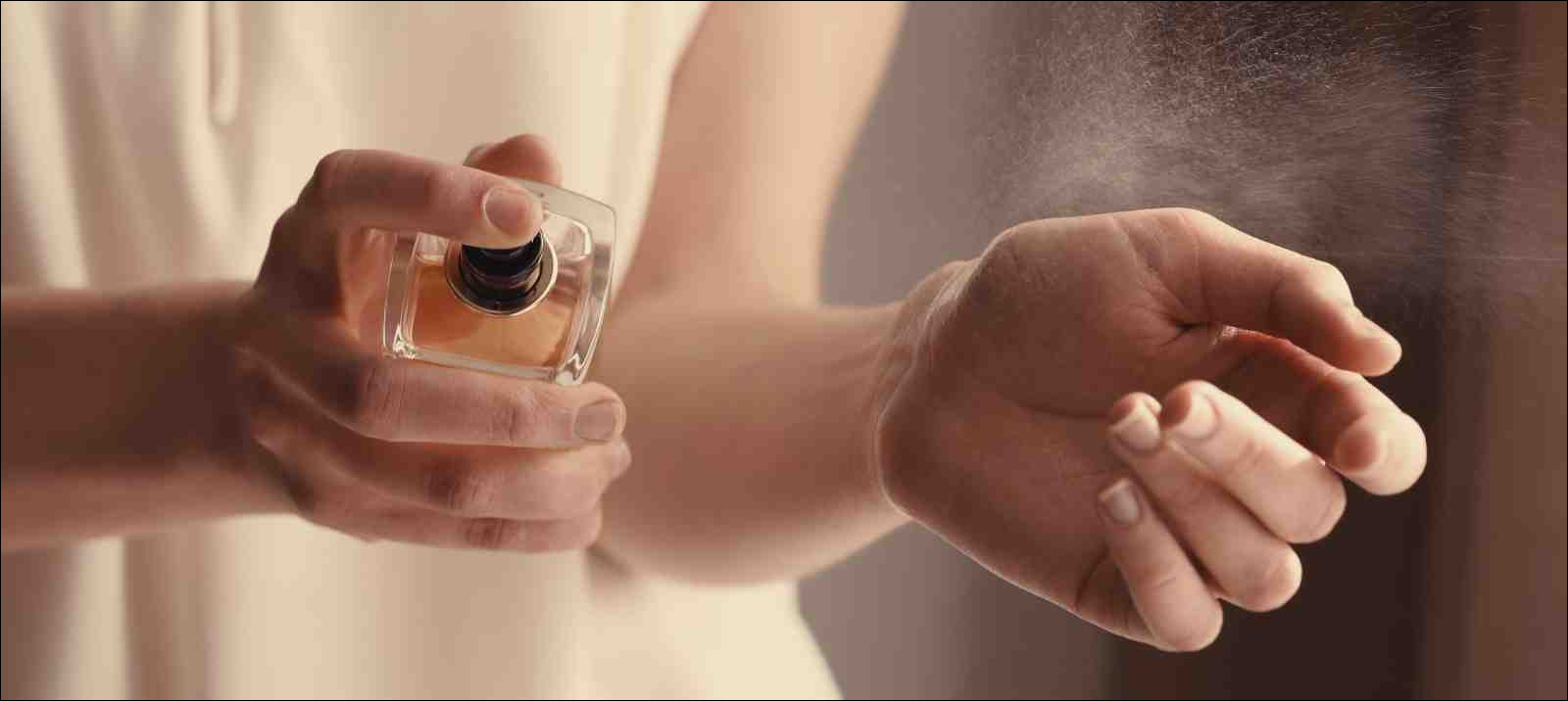 closeup of woman spraying perfume onto wrist