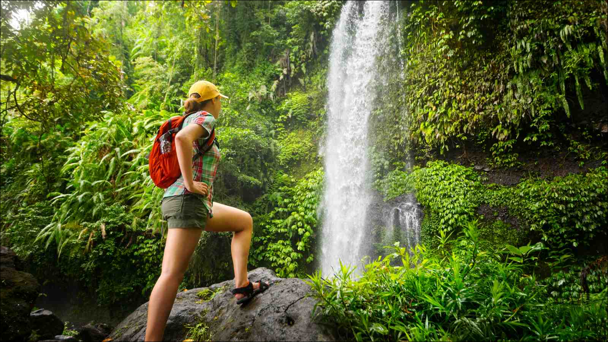 young woman backpacker looking at the waterfall in jungles