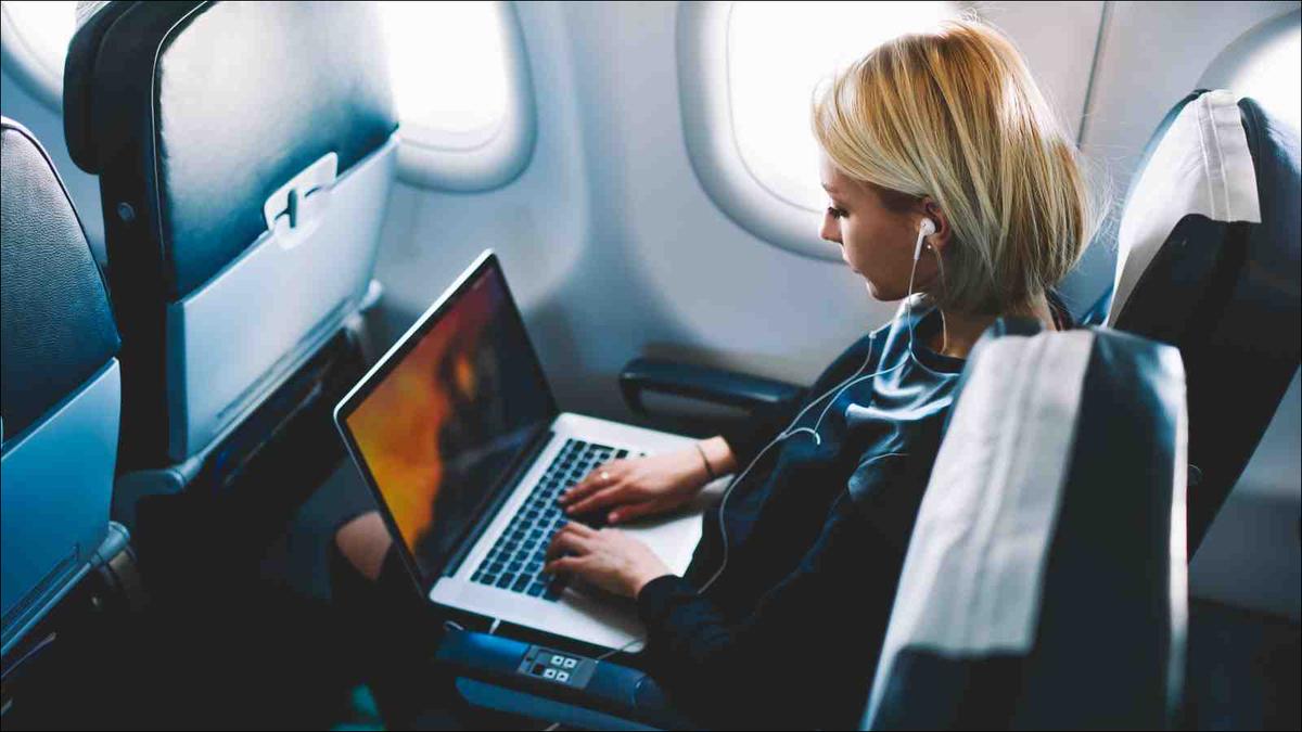woman sitting in airplane seat working on laptop