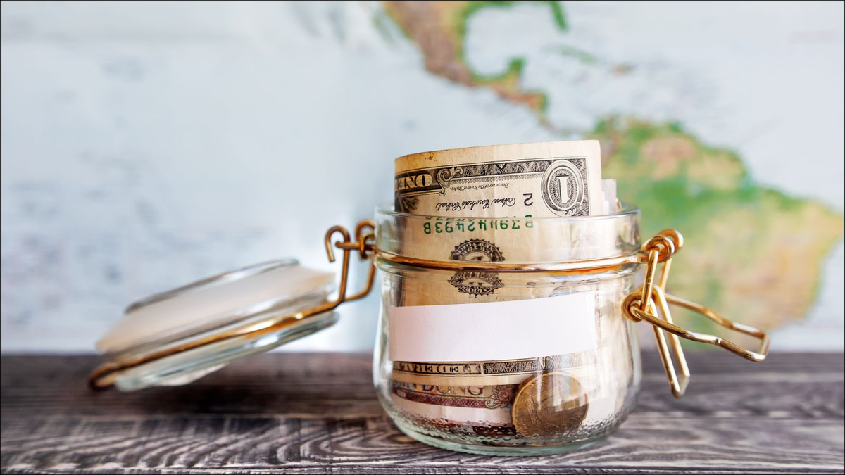 Glass jar with cash savings on wooden table and map as background