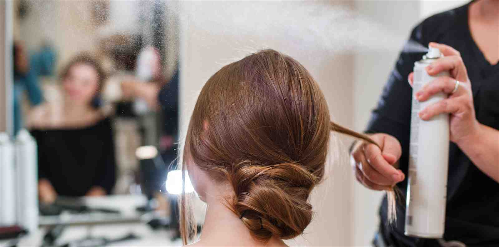 Hairdresser fixing woman's hair with hairspray