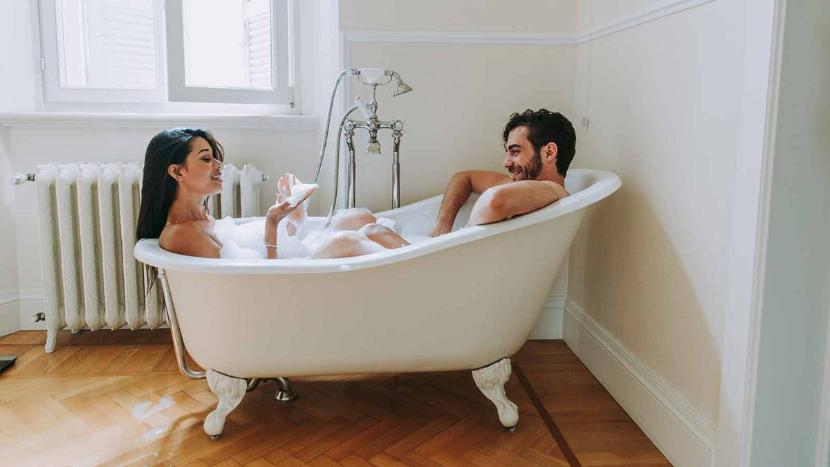 Couple soaking in a hot bath together to relax at the end of the day