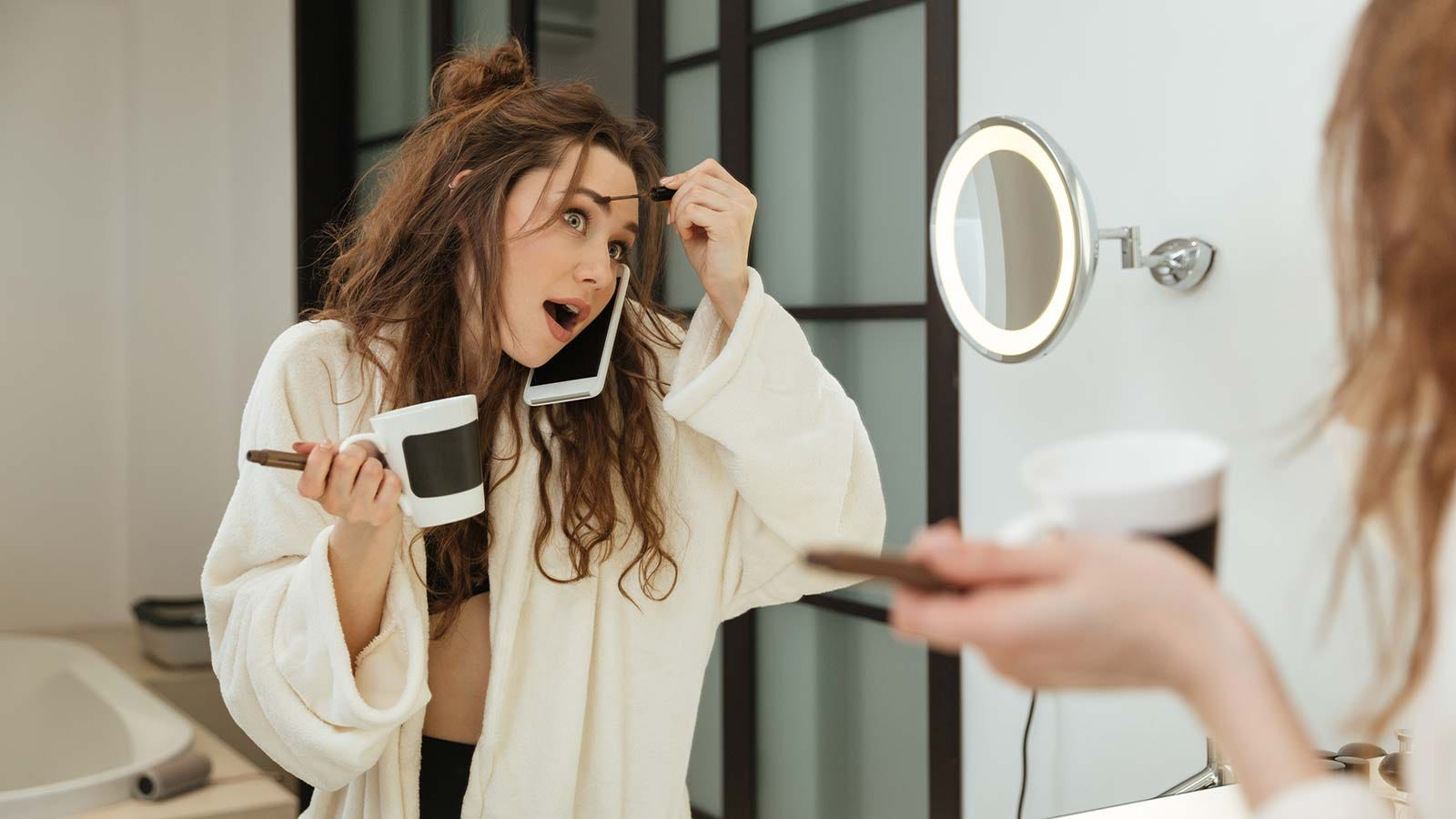woman getting ready in the morning, putting on her makeup in the bathroom