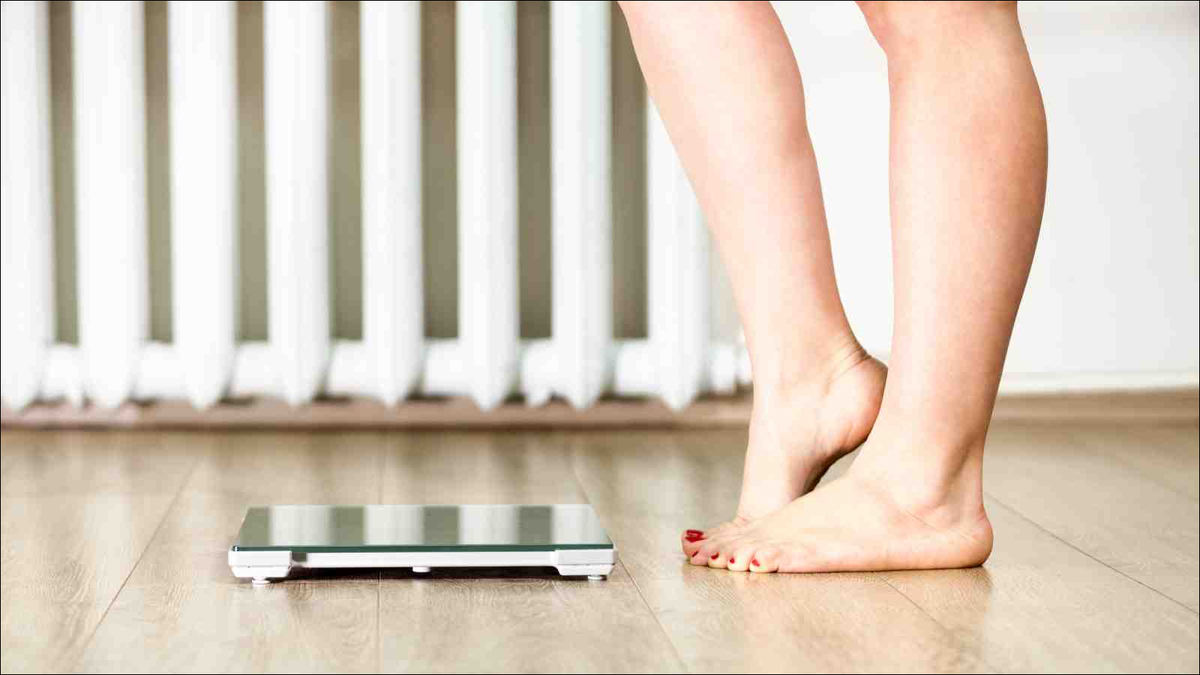 woman's legs standing in front of weight scales hesitating to step on