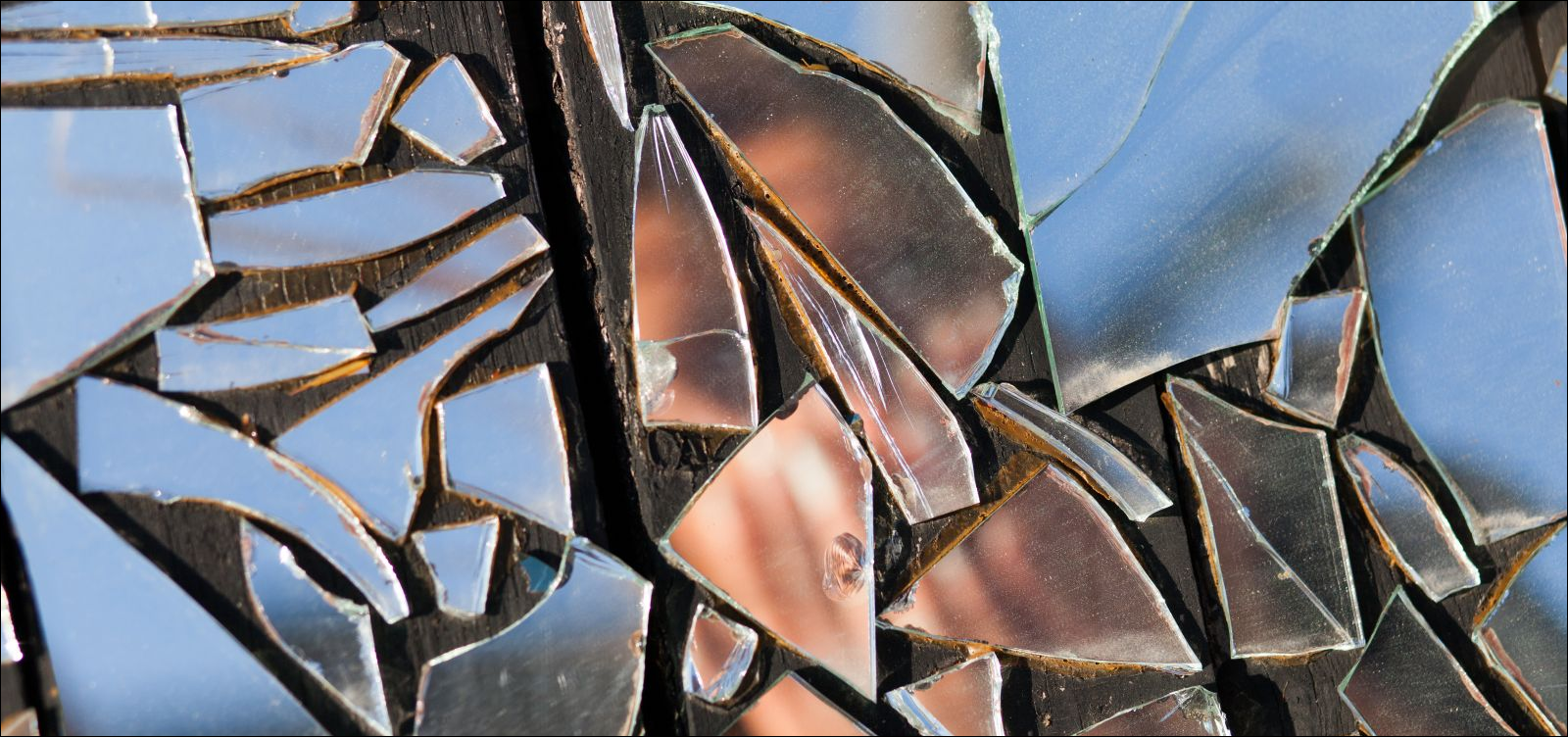 obscured image of a woman in broken mirror reflection