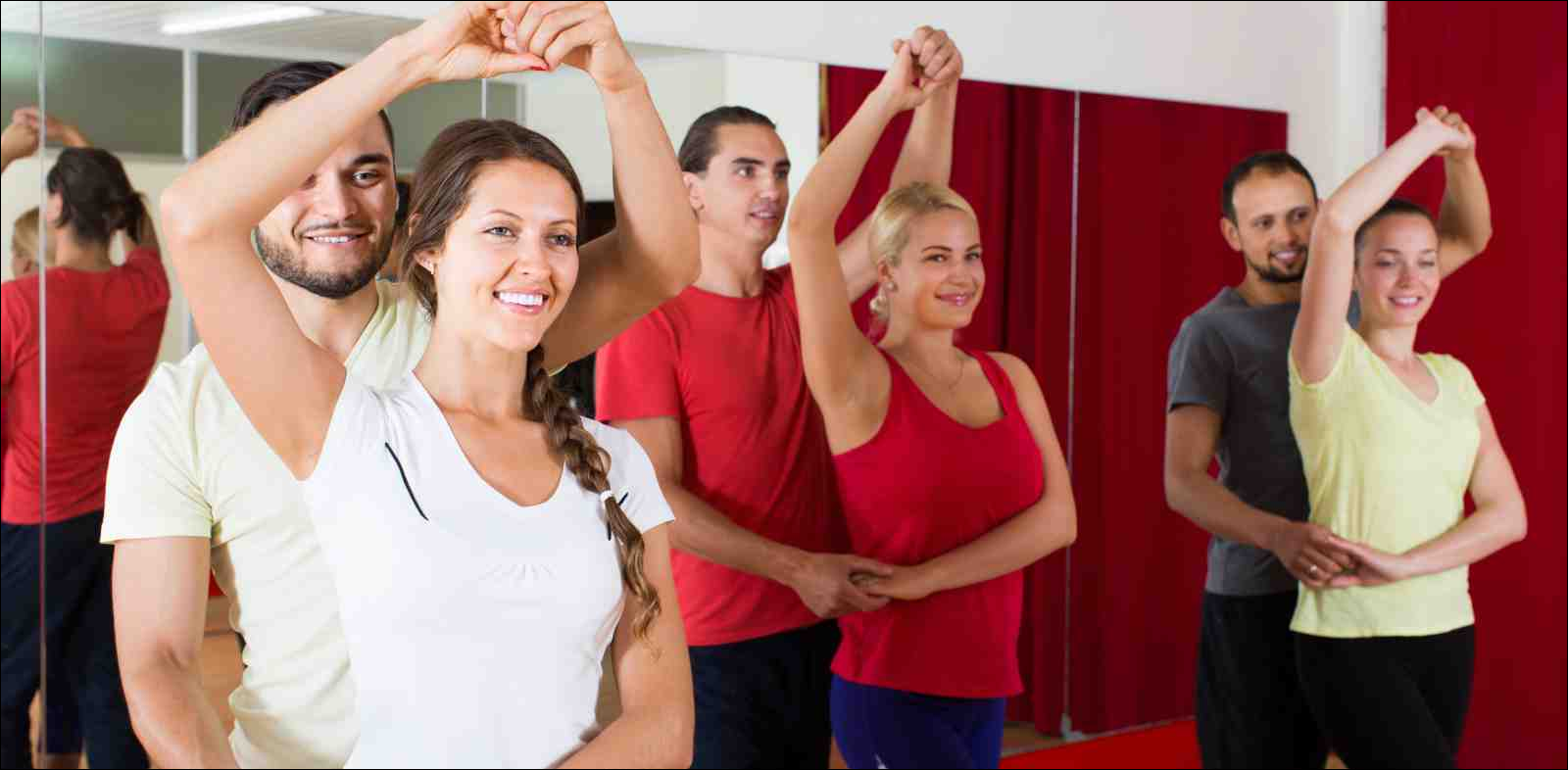 Group of adults dancing salsa in studio