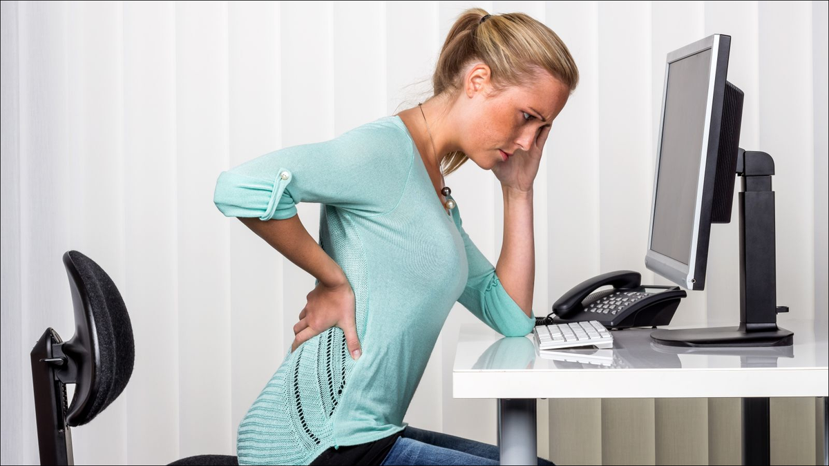 woman sitting at desk and has pain in the back