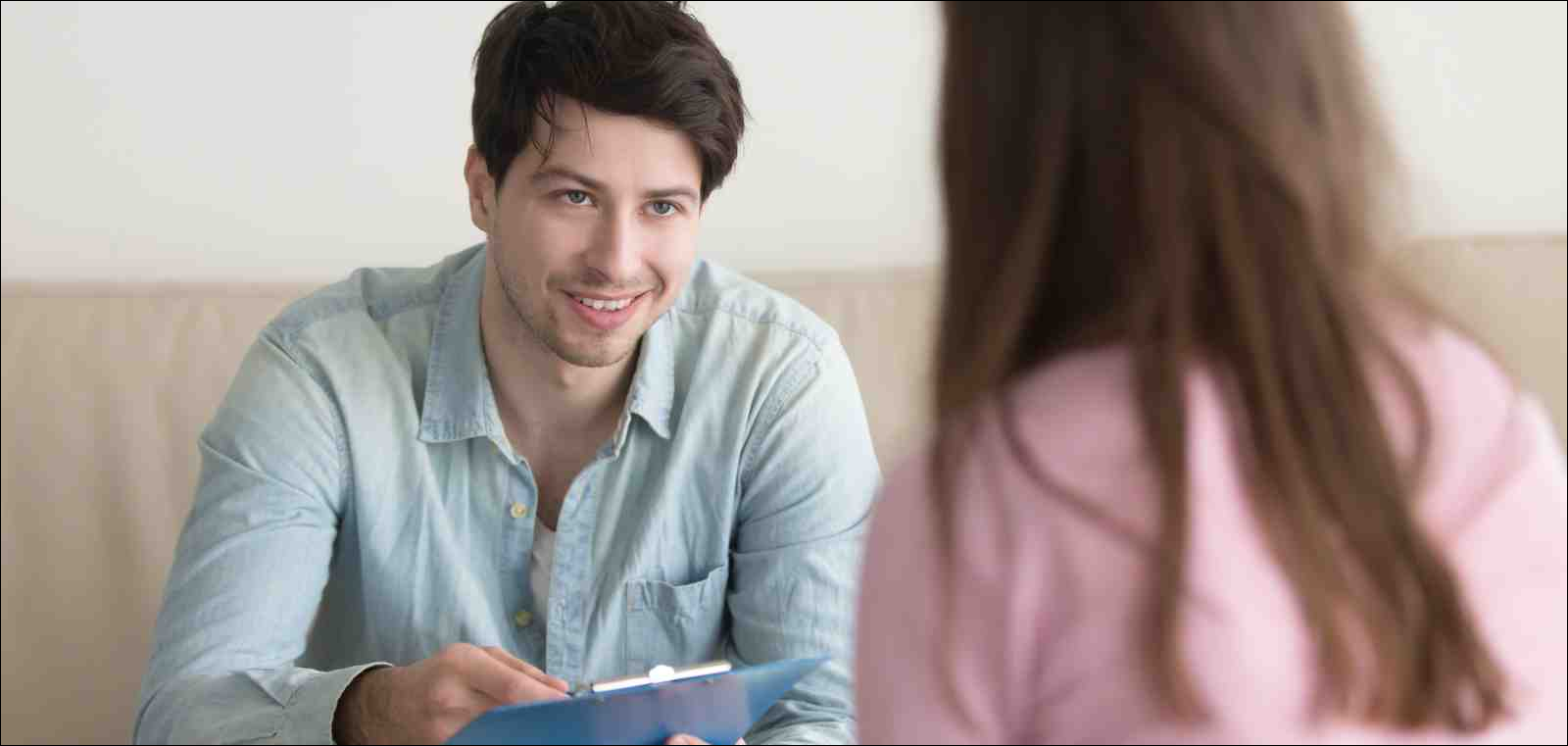 Young smiling man sitting on couch opposite woman, holding clipboard