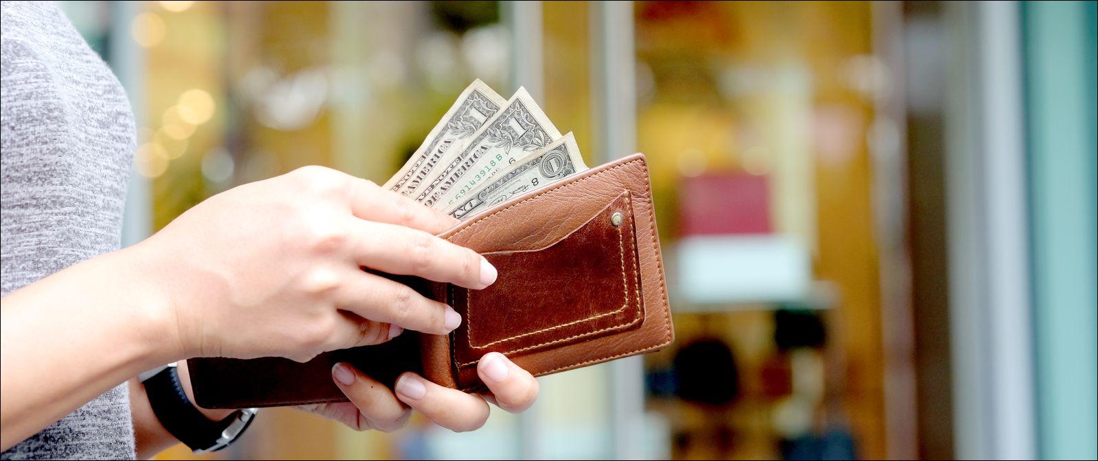 Woman pulling dollar bills from wallet