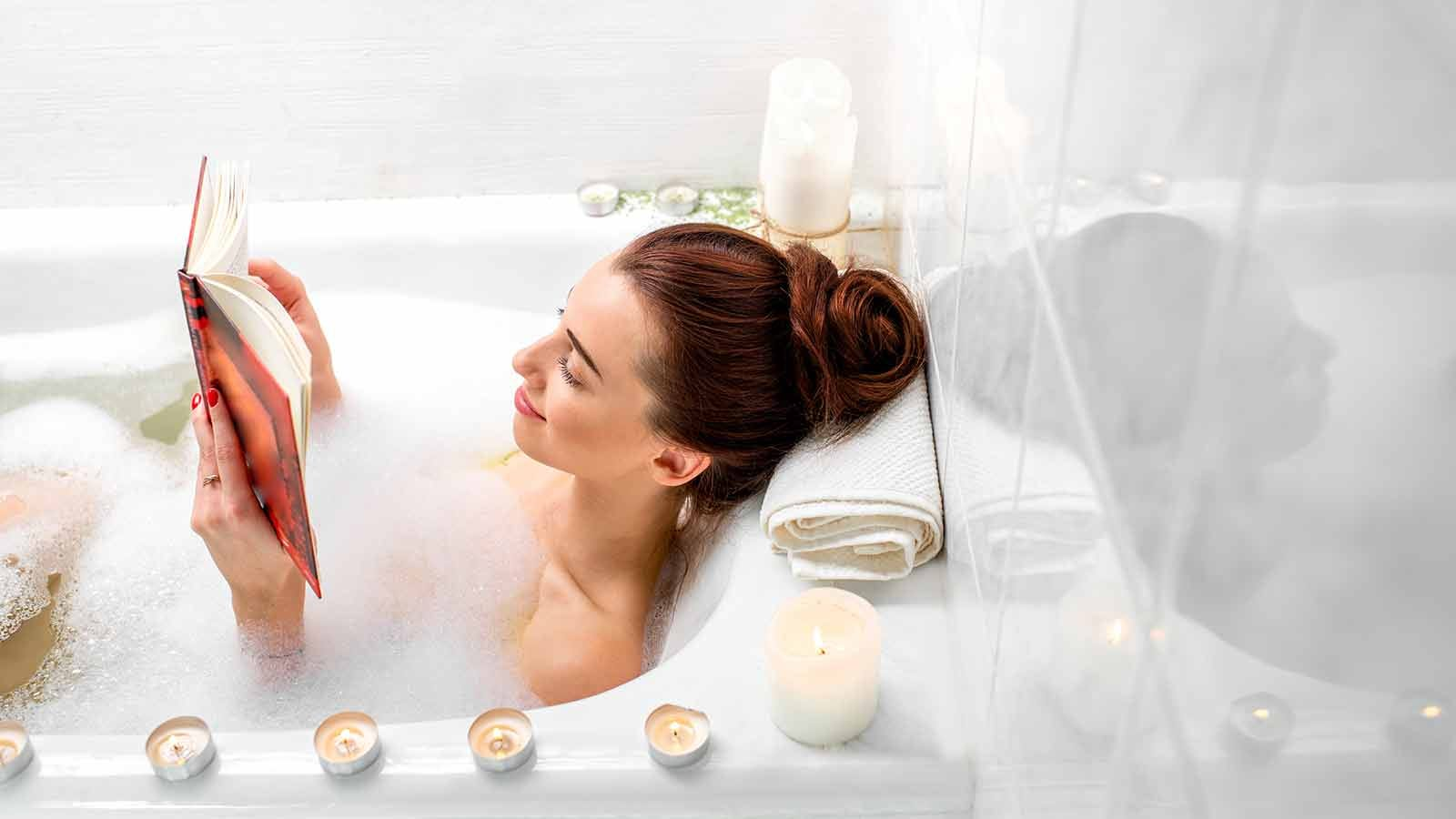 Woman soaking in the bathtub reading a book