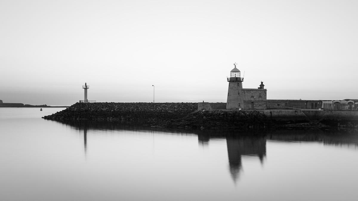 A photo a lighthouse on a harbor breakwall.
