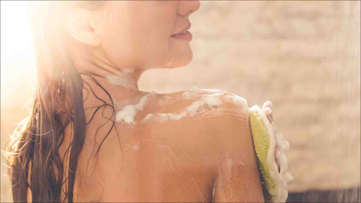 young woman in showed washing shoulder
