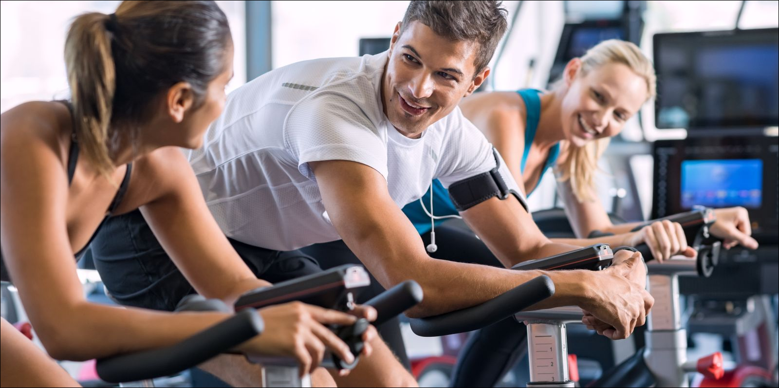 Young people talking and smiling while working out on bike at gym