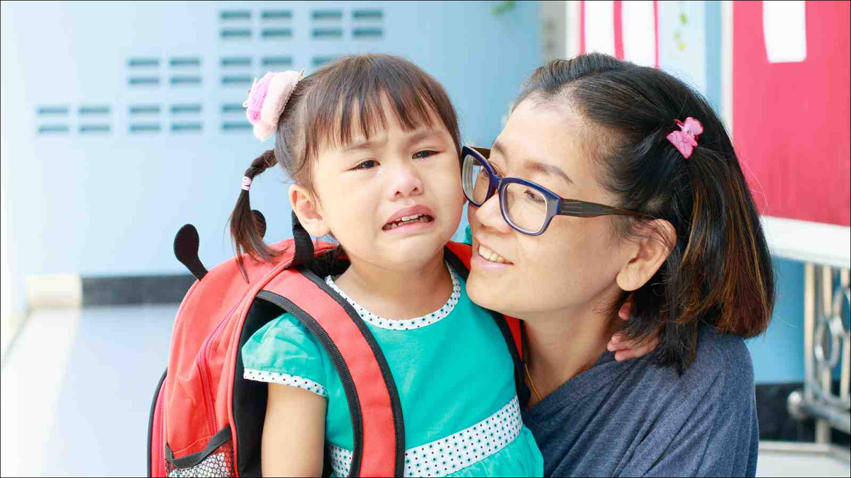 mother comforting crying daughter on first day of preschool