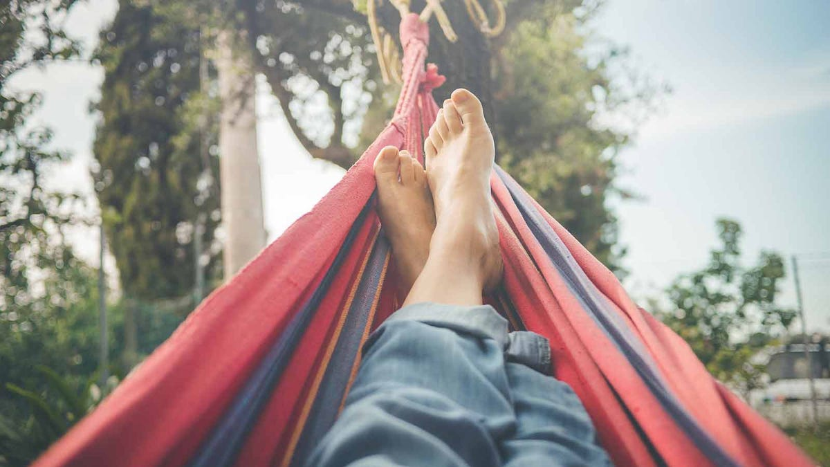 A person relaxing in a hammock with their bare feet in the sun