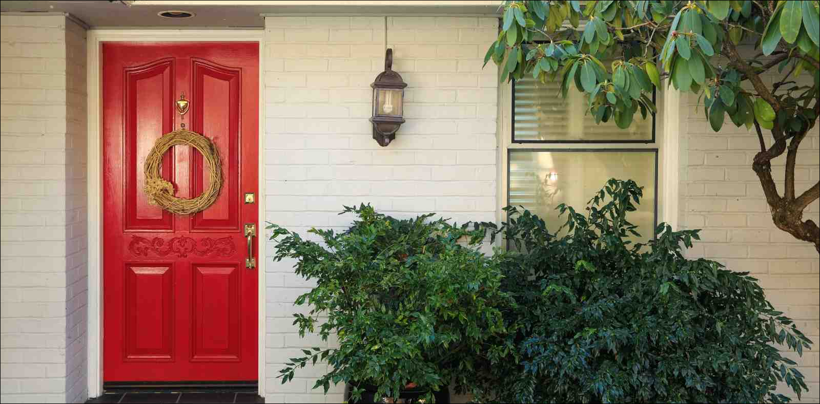 Front porch with white painted brick exterior, red entrance door accented with Door Wreath and finished with pot planter under wall lantern
