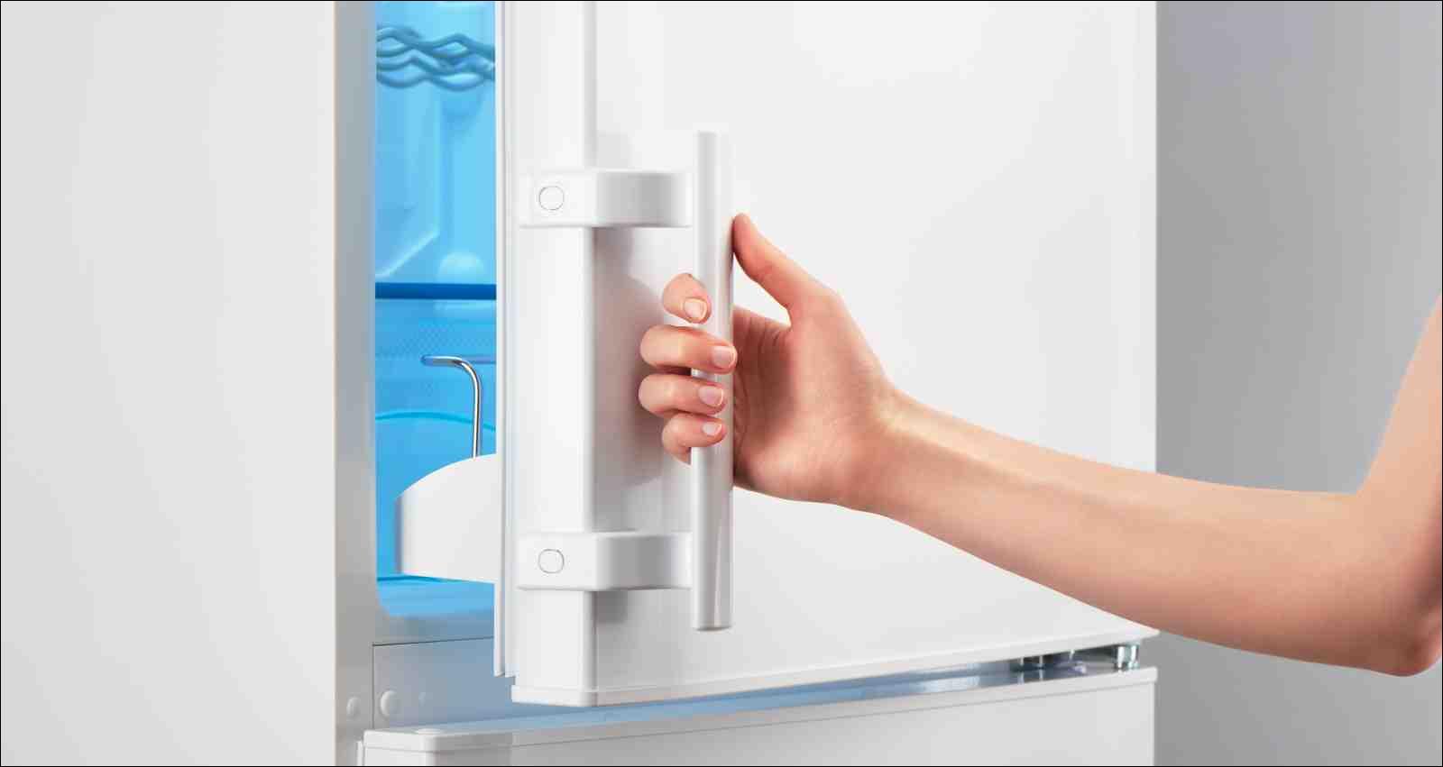 Female hand opening white refrigerator door