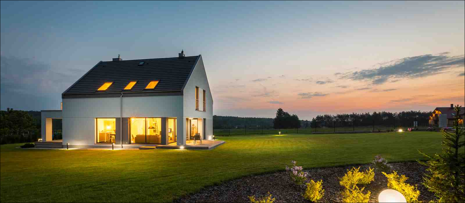 Photo of modern house with outdoor lighting, at night