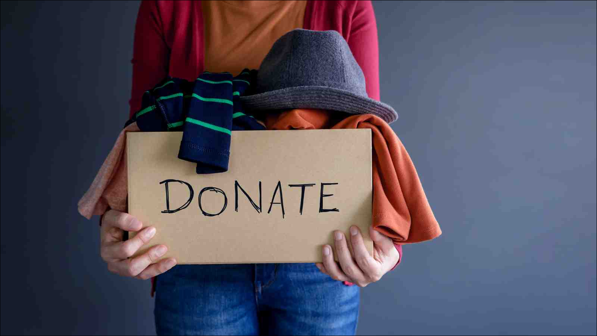 Woman holding a box full of clothes marked donate