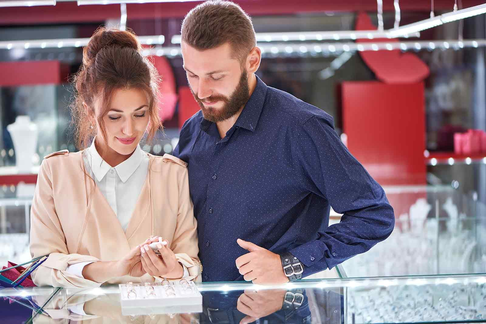 Happy couple looking at an engagement ring in a jewelry store