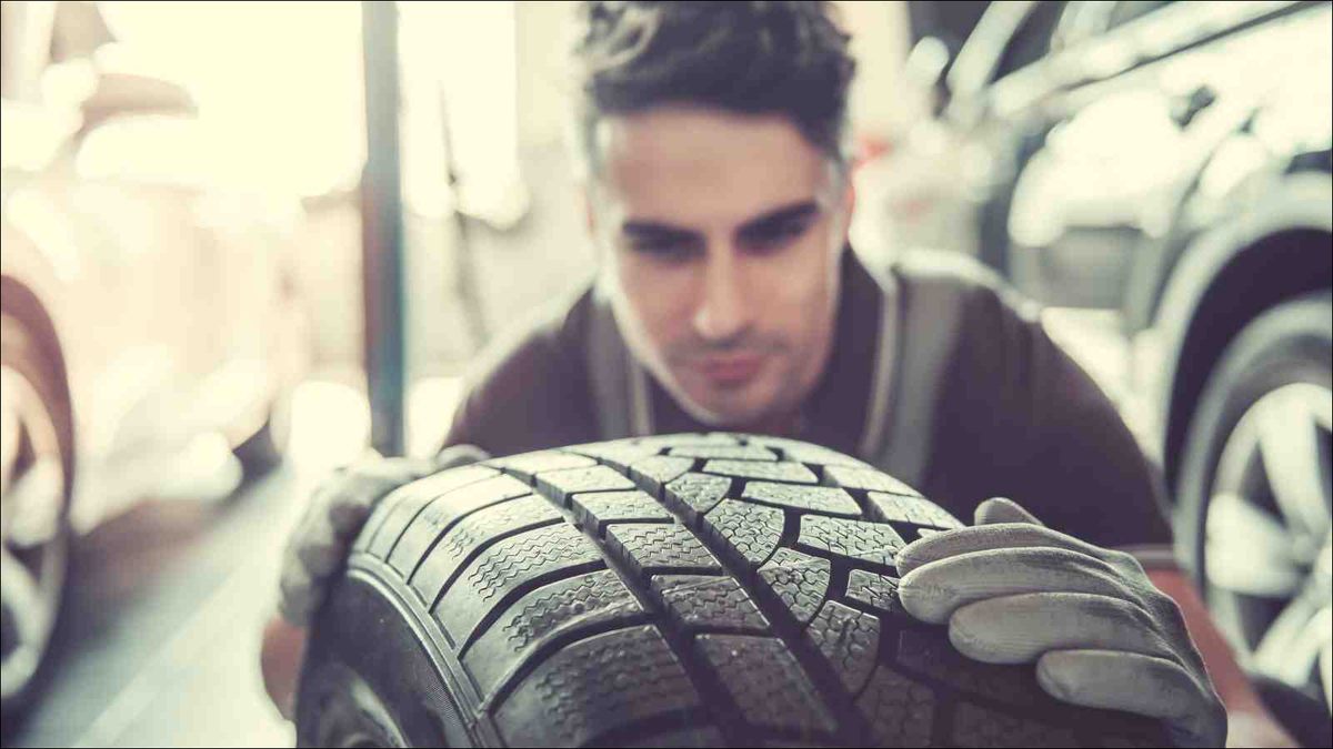 Young man inspecting tire
