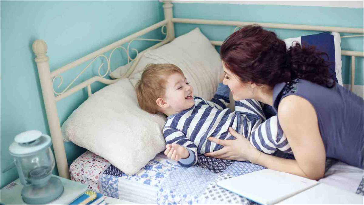 mother playing with two-year-old son in his new bed