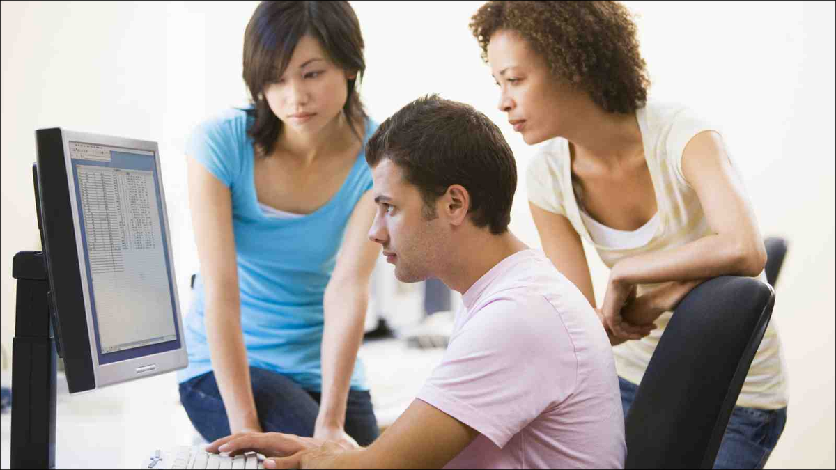 Three people in casual dress looking at monitor