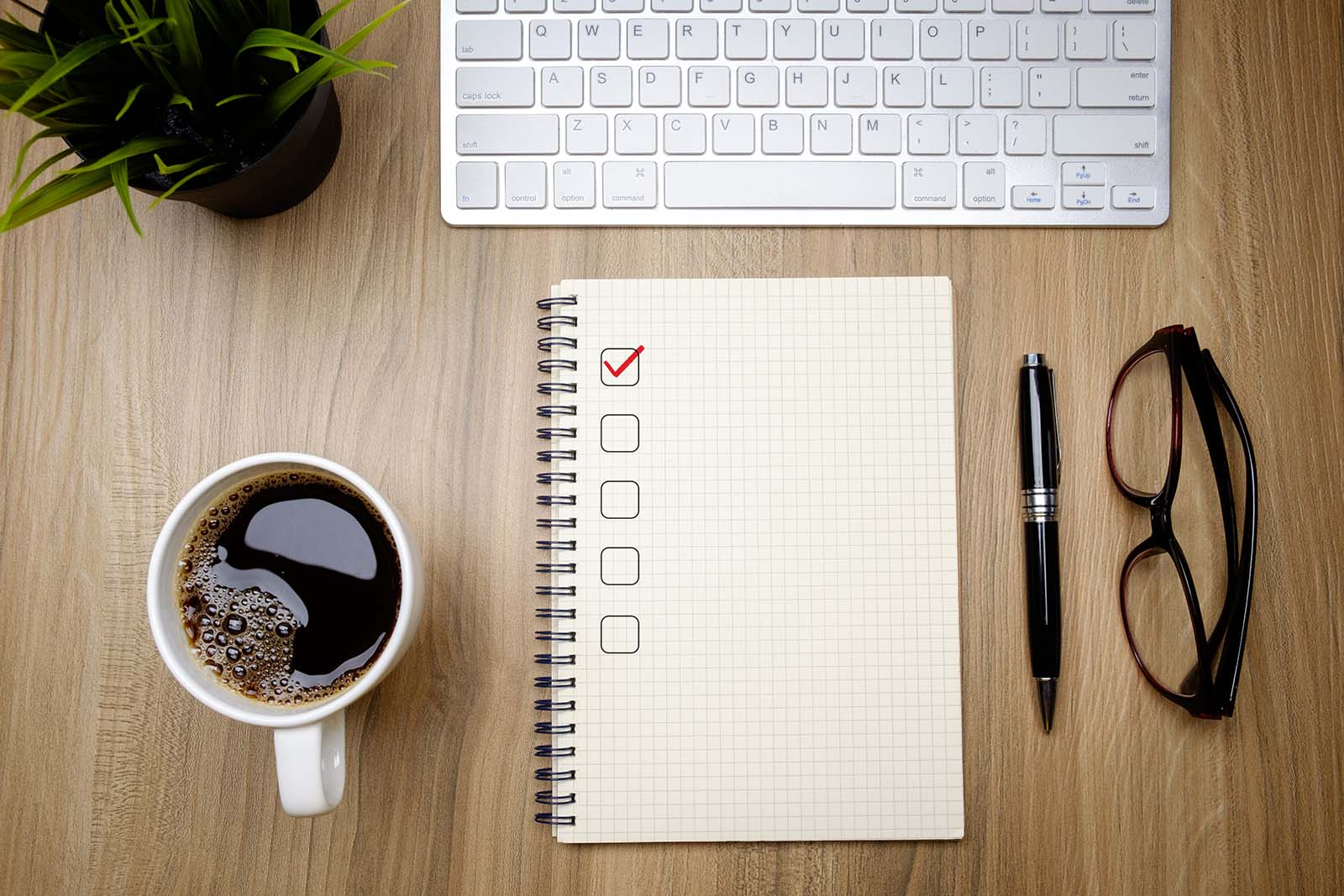 Checklist sitting on a desk with a keyboard, coffee, pen, and glasses